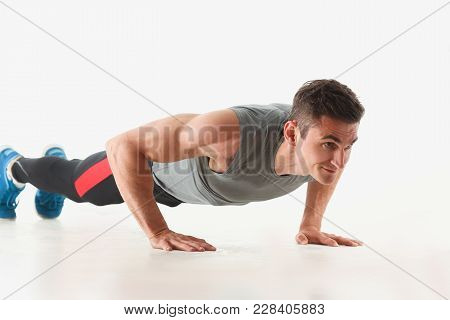 Fitness Man Wringing From The Floor Demonstrates Good Physical Exercises Isolated On White Backgroun