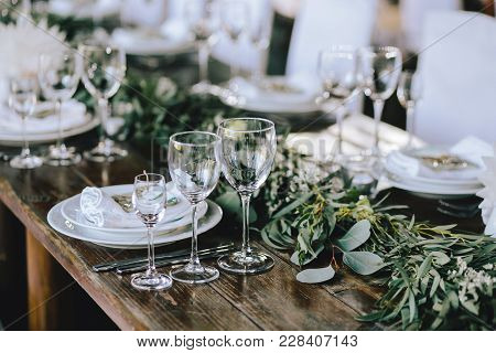 Decorated Elegant Wooden Wedding Table In Rustic Style With Eucalyptus And Flowers, Porcelain Plates