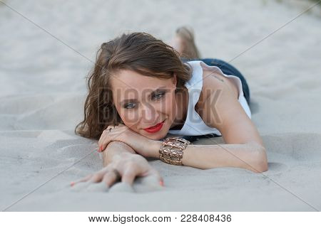 Young Beautiful Woman Lies On The Sand