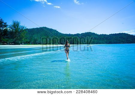 Young Beautiful Woman Running Across The Borneo Beach