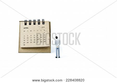 April. Two Thousand Eighteen Year Calendar And Miniature Plastic Man On White Background.