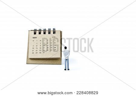 May. Two Thousand Eighteen Year Calendar And Miniature Plastic Man On White Background.