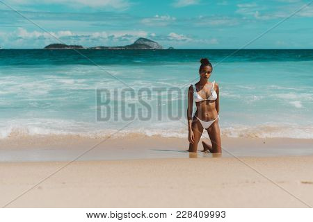 Exquisite Young African American Woman In White Swimsuit Is Standing On Her Knees On The Sand Near W