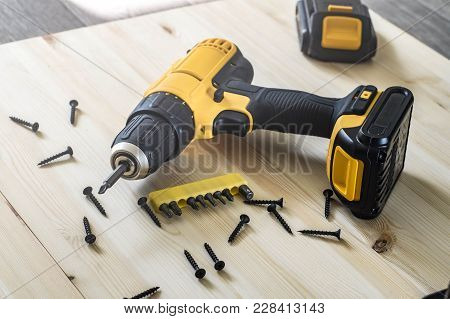 Working With A Hand Tool: A Yellow Screwdriver On A Wooden Table, Screws, A Set Of Bits.