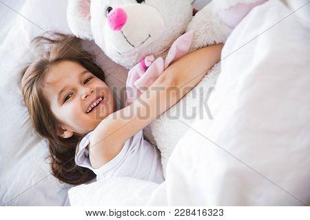 Beautiful Little Girl Hugging Her Teddy Bear In Bed A