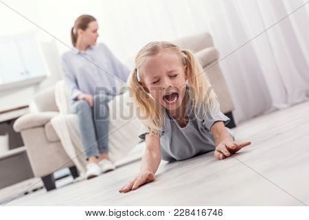 Listen To Me. Disobedient Naughty Unruly Girl Posing On Floor While Yelling And Closing Eyes