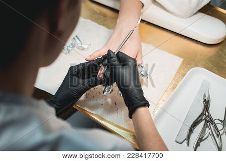 Close-up Of A Manicurist Removing Old Nail Polish With Some Acetone From The Woman Fingers. Patient