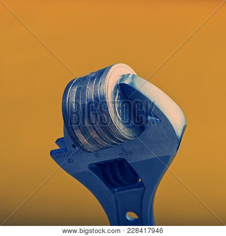 Stack Of Euro Coins Is Clamped. The Concept Of Financial Crisis Or Inflation.  Euro Money. Currency
