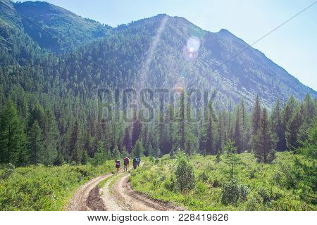 Group Of Travelers With Backpacks Walk Along A Trail Towards A Mountain Ridge By Sunny Day. Backpack