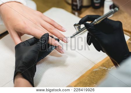 Closeup Shot Of A Woman In A Nail Salon Receiving A Manicure By A Beautician With Airbrush. Woman Ge