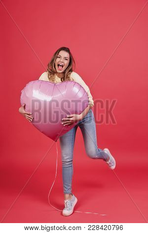 Feeling Playful.   Full Length Of Playful Young Woman Holding Heart Shaped Balloon And Smiling While