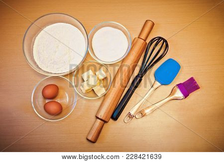 Flour, Eggs, Sugar, Butter And Kitchen Utensils On Table