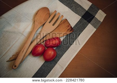 Wooden Kitchen Utensils And Fresh Tomatoes On Wooden Table