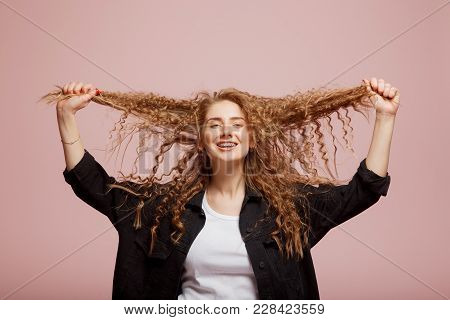 Girl With Curly Hair And Braces Pulls Her Hair. Concept Hair Straightening. Sick, Cut And Healthy Ha