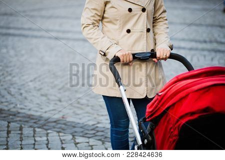 Young Mother Walking With Baby Carriage At The Street. Mother With A Stroller Walks Down The Street