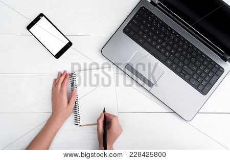 Top View On White Wooden Table With Open Blank Laptop Computer, Cell Phone, Empty Diary And Girl's H