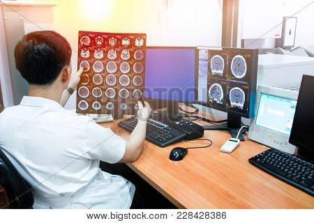 Doctor Working With Ct Scan Monitor And Computer In Radiology Room.