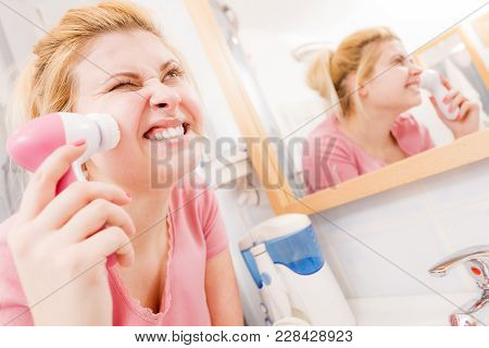 Deep Cleaning Face Tools Concept. Scared Screaming Woman Using Facial Cleansing Brush Machine.