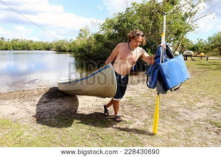A Young Man Is Pulling His Old Aluminum Canoe Out Of A River In The Everglades, On A Sunny Summer Da