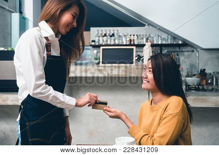 Young Asian Female Make A Payment To Coffee Shop Owner By Credit Card With A Background Of Beverage