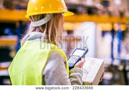 Warehouse woman worker or supervisor with barcode scanner. A mobile handheld PC with barcode scanner. poster