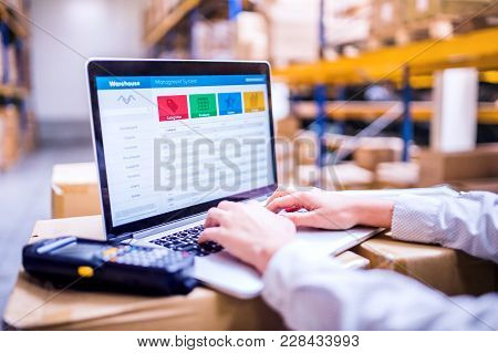 Unrecognizable Young Woman Warehouse Worker Or Supervisor Working On A Laptop.