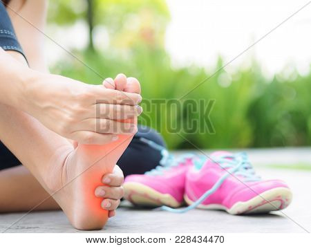 Soft Focus Woman Massaging Her Painful Foot While Exercising.   Running Sport Injury Concept.