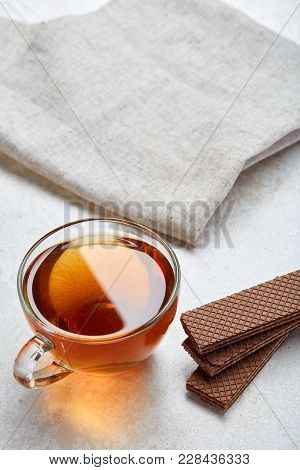 Top View Close Up Picture Of Earl Grey Or Black Tea In Transparent Glass Cup With Cookies Pieces Nex