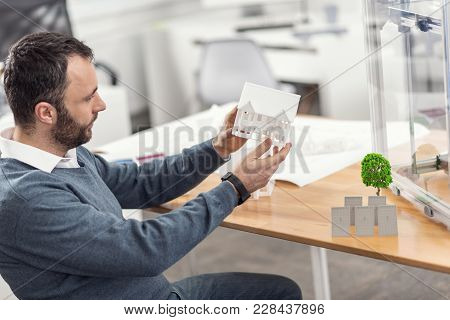 Impeccable Result. Handsome Dark-haired Engineer Scrutinizing A Miniature 3d Model Of A House After