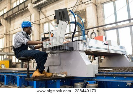 Profile View Of Young African American Worker Wearing Overall And Checked Shirt Operating Machine Un