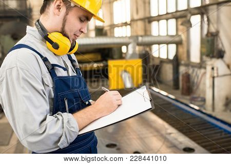 Profile View Of Young Bearded Technician Wearing Protective Helmet And Overall Standing At Spacious