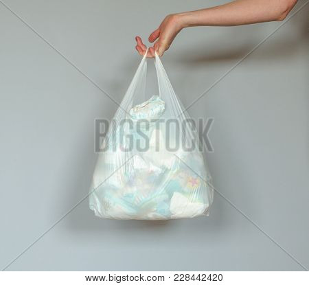 Woman Hand Holding A Plastic Bag Full Of Dirty Used Baby Diapers