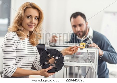 True Professional. Pretty Young Woman Posing For The Camera While Holding A Filament Spool Connected