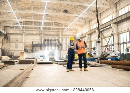 African American Engineer Wearing Reflective Vest And Hardhat Using Digital Tablet While Discussing