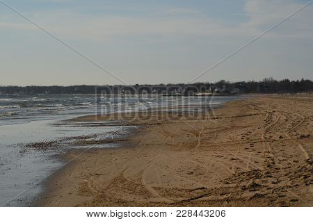 Some Waves Hitting The Beach At Low Tide