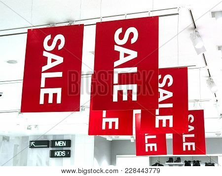 Sale Signs Are Hanging Under Ceiling In Clothing Shop