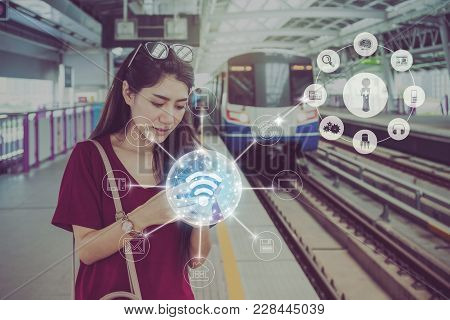 Asian Woman Passenger With Casual Suit Using The Social Network Via Smart Mobile Phone In The Skytra