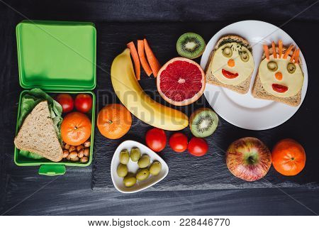 School Lunch Boxes With Sandwich And Fresh Vegetables, Nuts And Fruits On Blackbackground. Healthy E