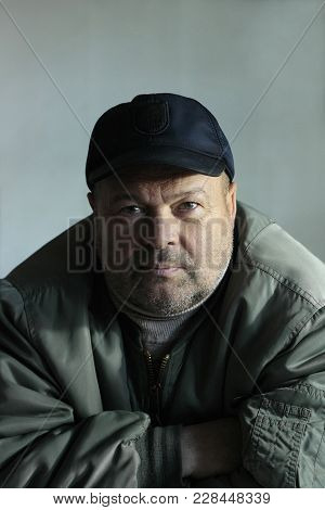 Angry Middle-aged Man With  Stubble On  Face In Green Jacket And Blue Cap Looks Directly Into The Le