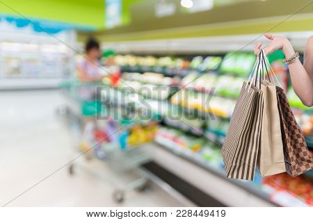 Holding Shopping Bags By Hand On Supermarket With Abstract Blurred Photo Of Store With Trolley In De