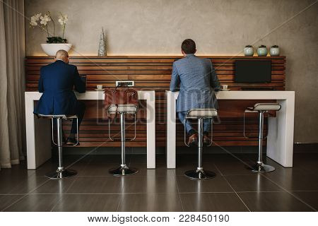 Rear View Shot Of Two Businessmen Sitting At Free Internet Service Counter In Airport Lounge. Busine