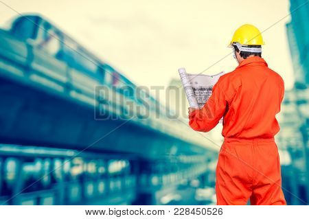 Portrait Of Asian Engineers Looking At The Blueprint On Abstract Blurred Photo Of Sky Train, Transpo