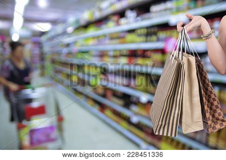 Holding Shoping Bags By Hand On Supermarket With Abstract Blurred Photo Of Store With Trolley In Dep