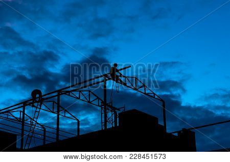 Silhouette Of Carpenter Working On Top Of The Roof Structure