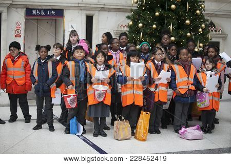 London, Uk - December 22, 2017: Children In Orange Waistcoats Sing Christmas Carols, Collect Money F