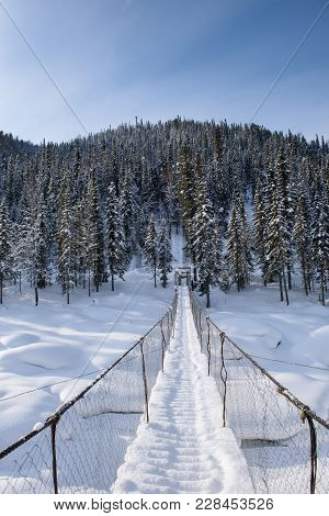 Suspension Bridge Over A Frozen River In The Winter In The Mountains.