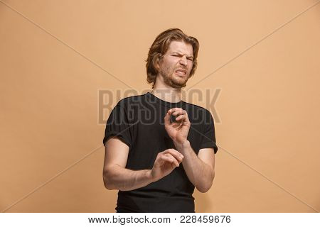 Young Man With Disgusted Expression Repulsing Something, Isolated On The Pastel
