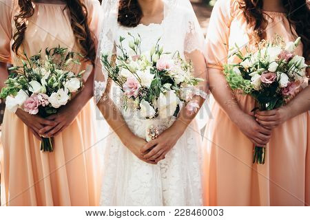 Two Girlfriends And A Bride Hold Beautiful Wedding Bouquets In Their Hands