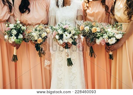 Four Girlfriends And A Bride Hold Beautiful Wedding Bouquets In Their Hands