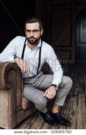 Handsome Bearded Man In Eyeglasses And Suspenders Sitting In Armchair